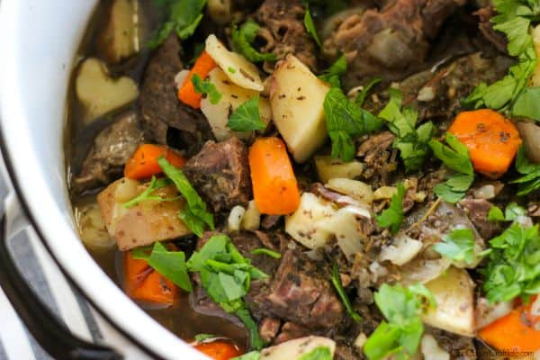 white pot of slow cooker beef stew with potatoes, carrots, beef and herbs for delicious whole30 recipes